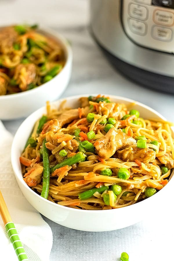 White bowl filled with Asian Chicken and noodles.