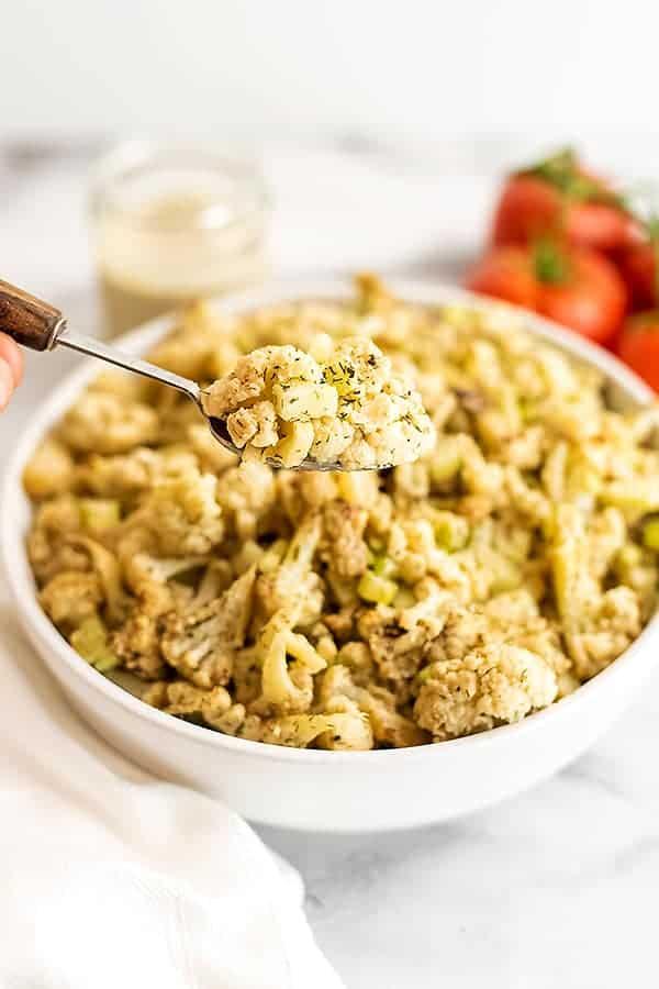 Spoon scooping a serving of cauliflower potato salad.