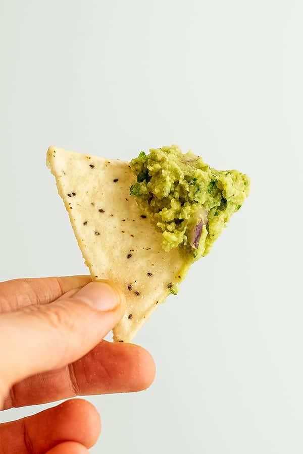 Single chip with roasted cauliflower guacamole on top.