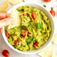 Single tortilla chip being dipped in large bowl of guacamole.