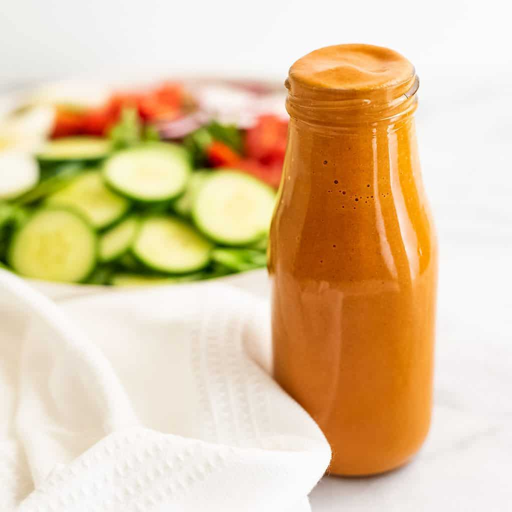 French dressing in a glass bottle with salad in background.