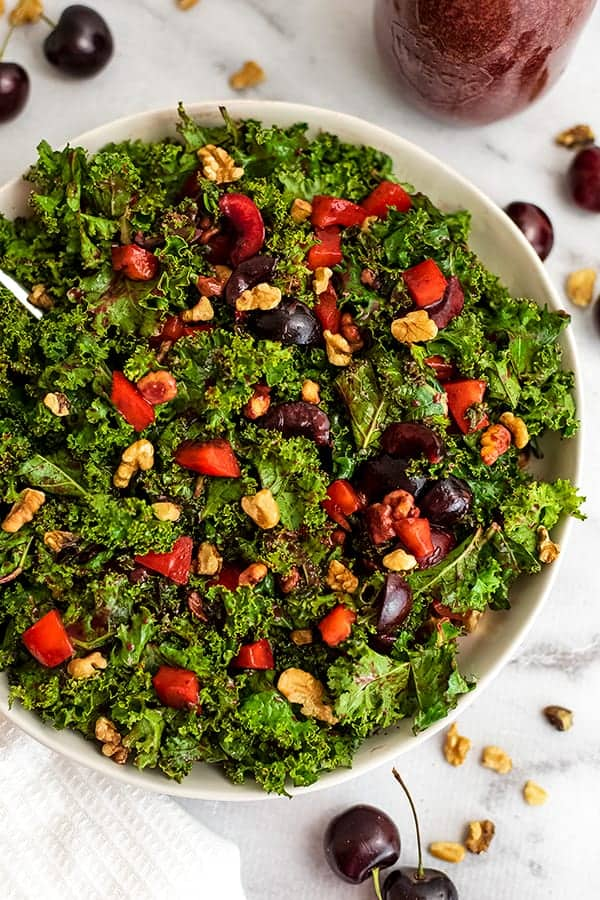 Large bowl filled with cherry kale salad with dressing in the back.