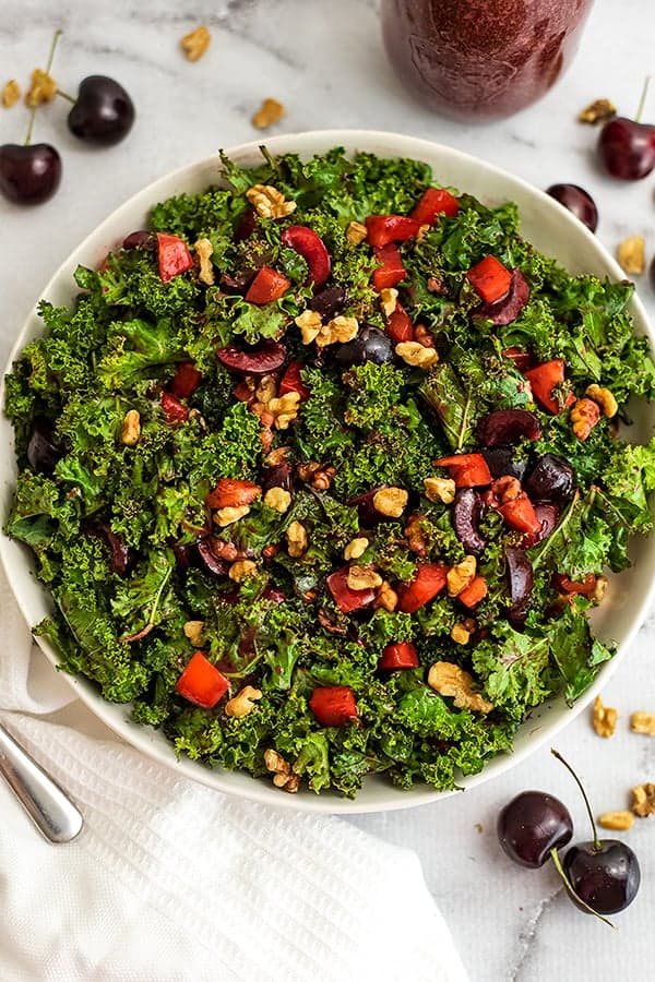 Cherry kale salad in a large white bowl with cherries around the bowl.