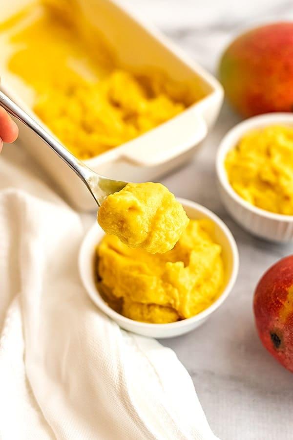 Spoonful of mango frozen yogurt over a bowl.
