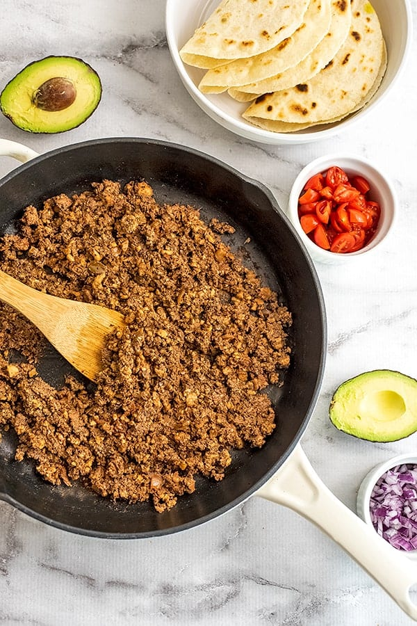 Cast iron skillet with vegan walnut taco meat surrounded by avocado.