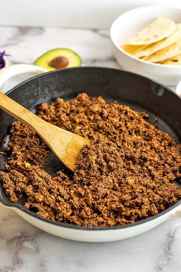 Wooden spoon in skillet with vegan walnut taco meat.