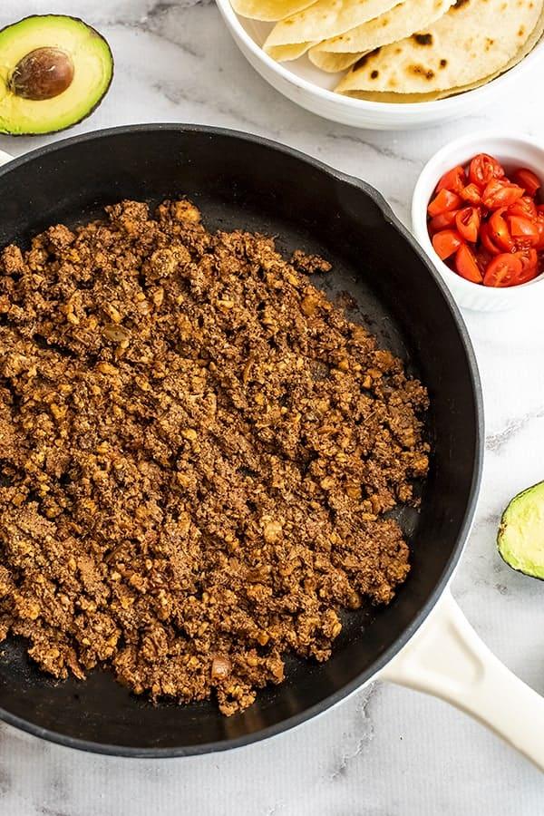 Mushroom walnut taco meat in skillet with tortilla shells.