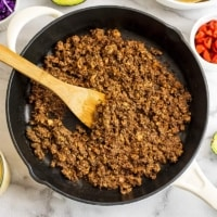 Skillet with mushroom walnut taco meat and wooden spoon.