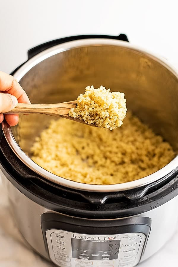 Large spoon of quinoa over the instant pot filled with quinoa.