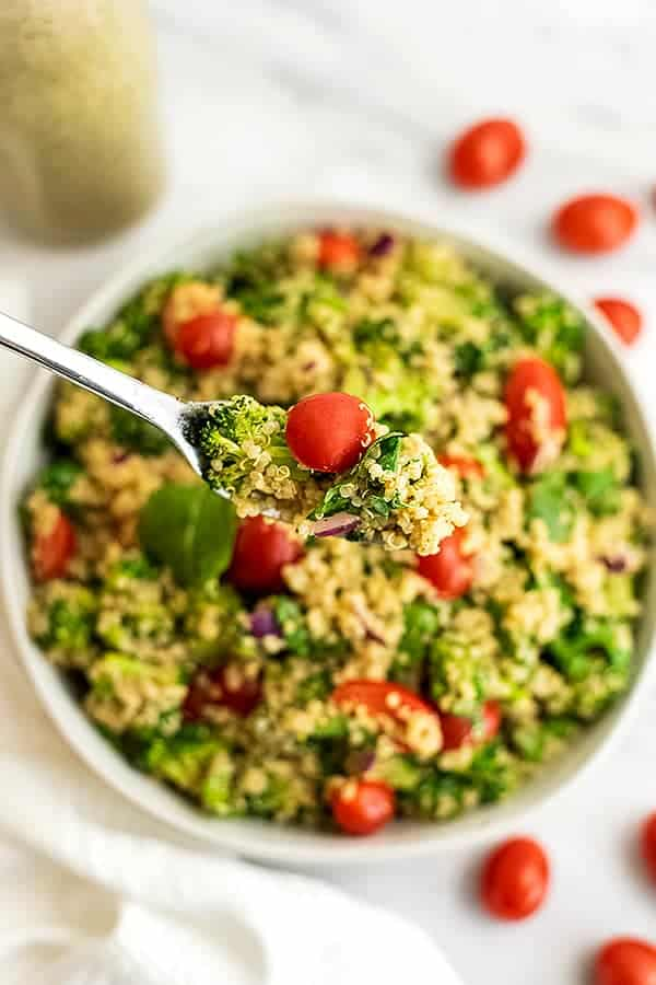 Fork scooping a bite of Italian quinoa salad from bowl.