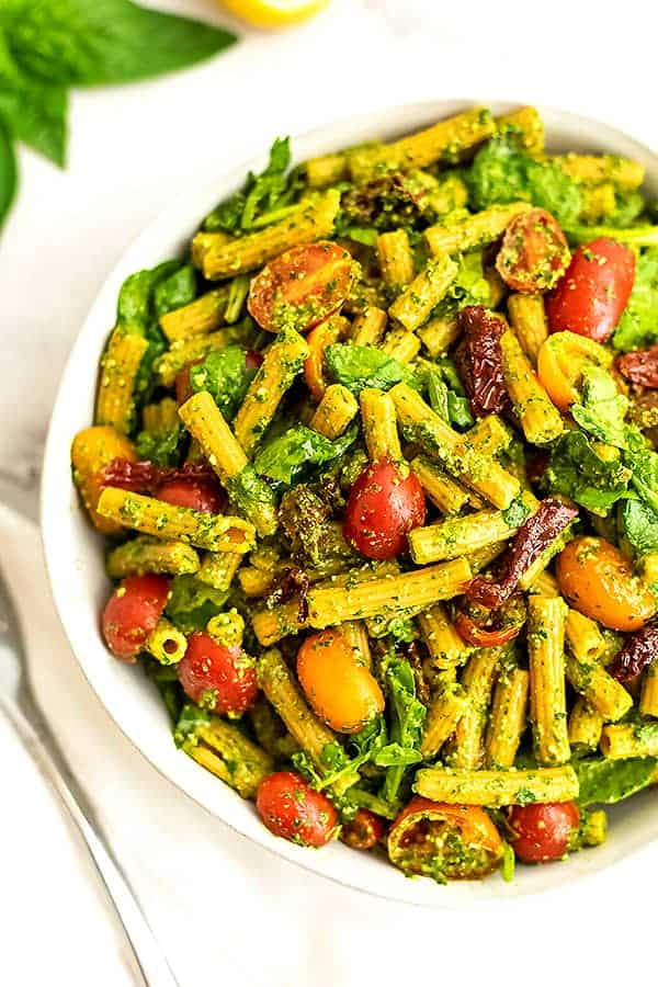 Large bowl filled with pesto pasta salad with sun dried tomatoes.