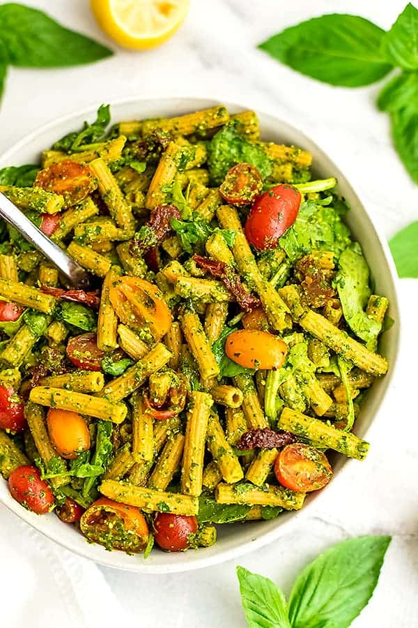 Fork in bowl of pesto pasta salad with sundried tomatoes.