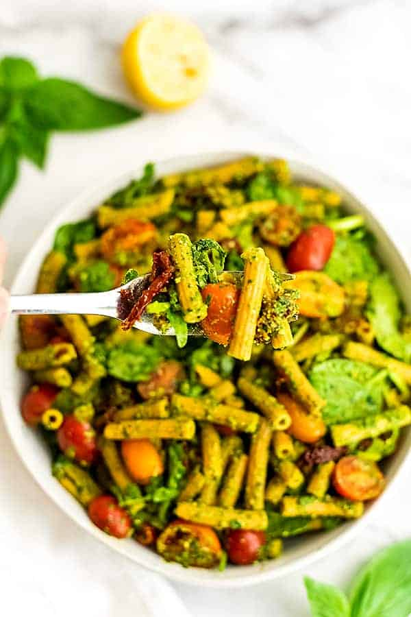Fork full of pesto pasta salad with sun dried tomatoes.