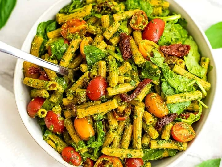 Pesto pasta salad with sun dried tomatoes with fork in the bowl.