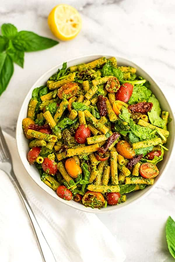 Bowl of pesto pasta with sundried tomatoes with fork on side.