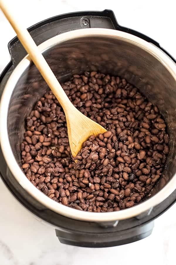 Wooden spoon in Instant Pot filled with black beans.