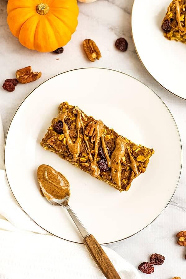 Single pumpkin oatmeal breakfast bar on white plate.