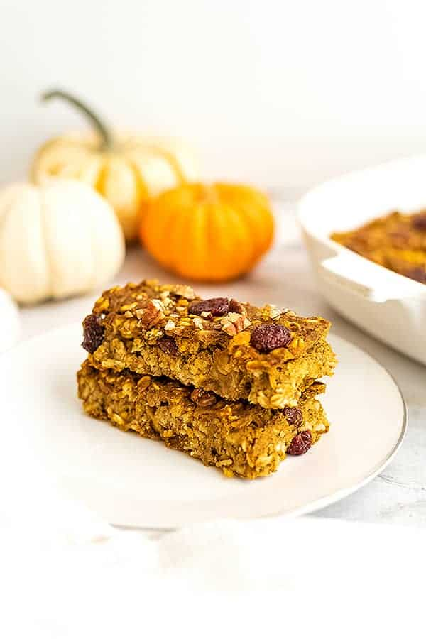 Two pumpkin oatmeal breakfast bars stacked on top of a plate.
