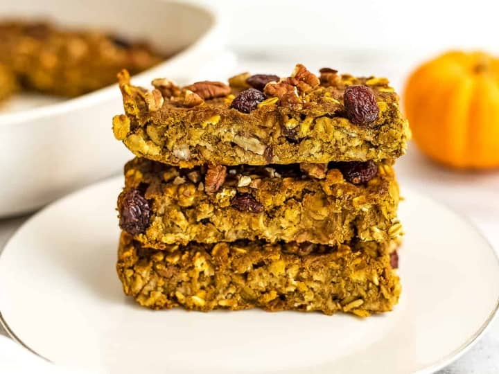 3 pumpkin breakfast bars stacked on a white plate.