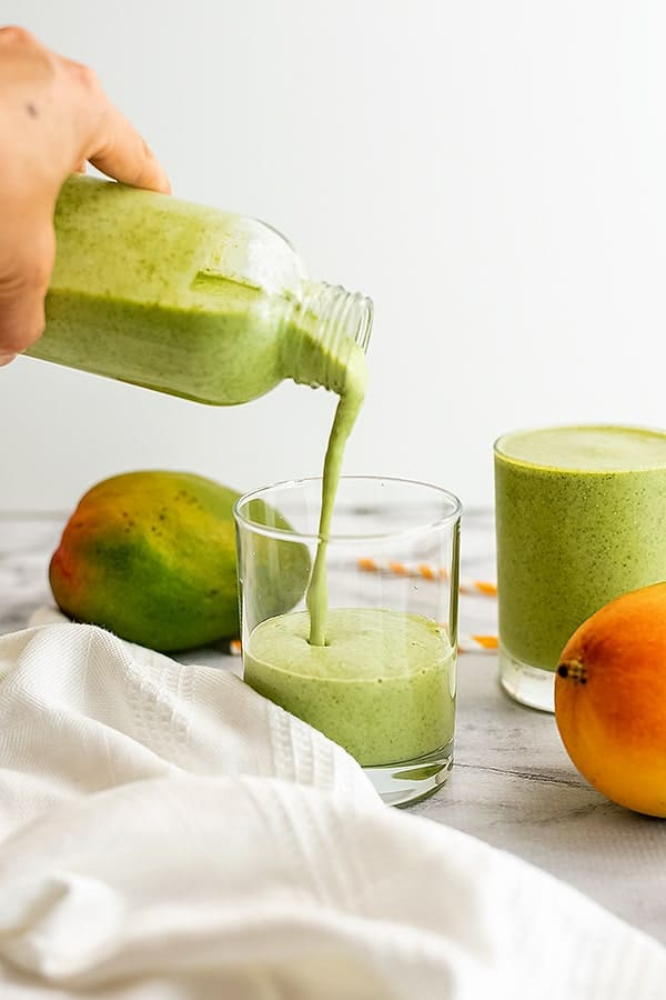 Mango kale smoothie being poured into a glass.
