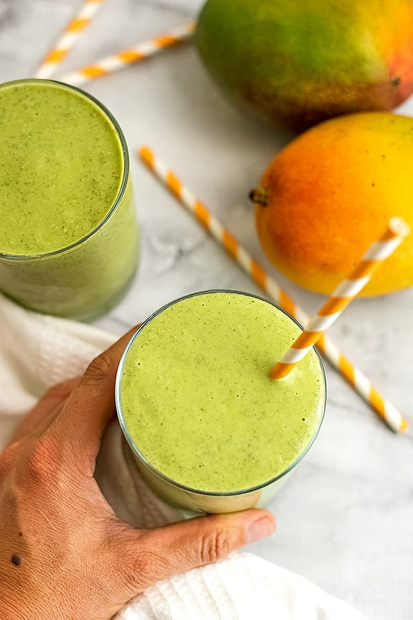 Hand holding a glass of mango kale smoothie.