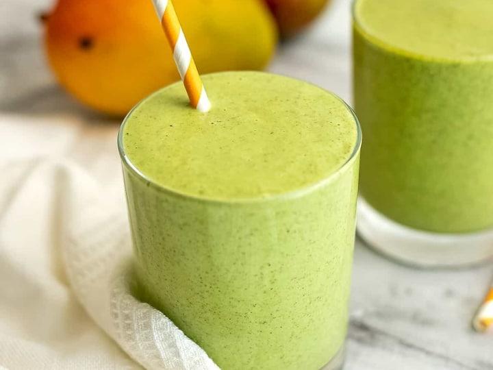 Mango kale smoothie with mangoes in background.
