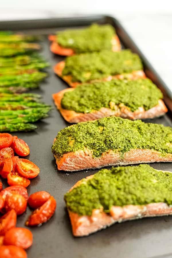 Pesto salmon baked on a sheet pan.
