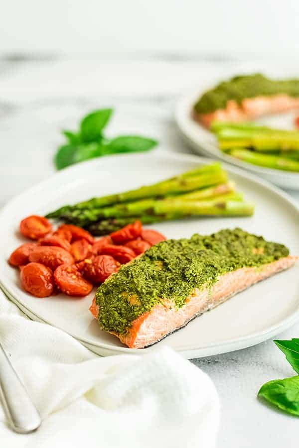 Pesto crusted salmon with veggies on a white plate.