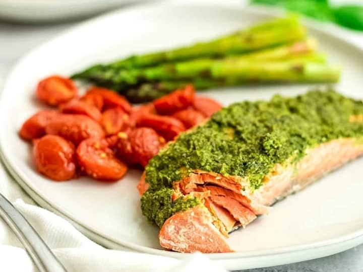 Pesto salmon flaked on the plate with veggies.