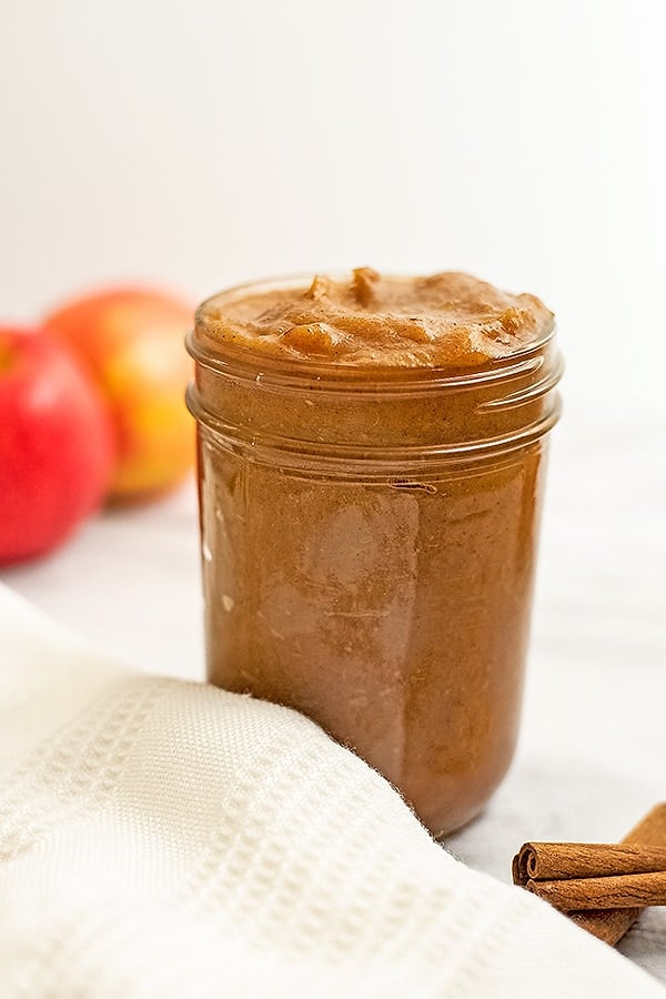 Large jar of apple butter with apples behind the jar.