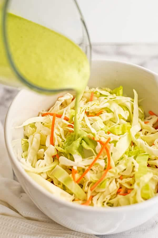 Creamy cilantro lime dressing poured over cabbage.