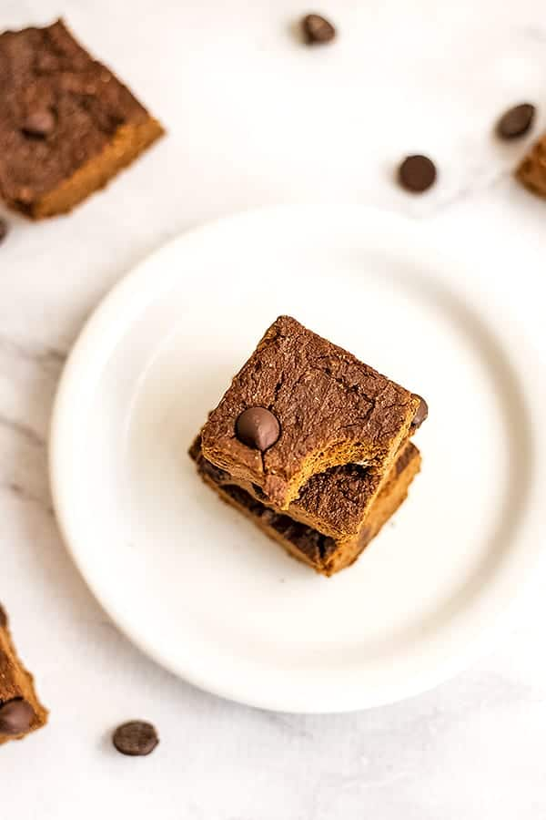 Two brownies on a plate with chocolate chips in the background.