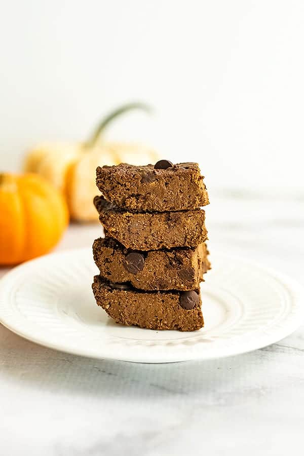 Stack of 4 pumpkin protein brownies on a plate.