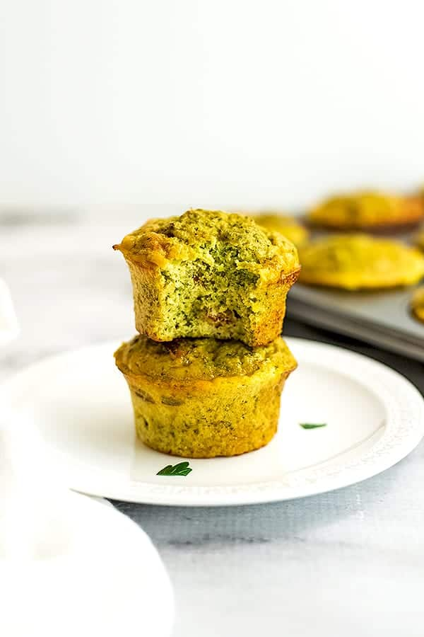 Two cheesy broccoli egg muffins stacked on a plate.