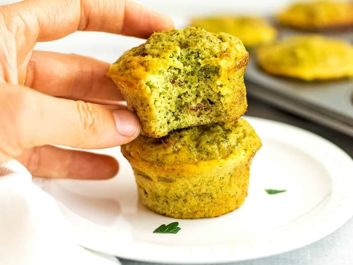 Hand holding broccoli cheese egg cups.