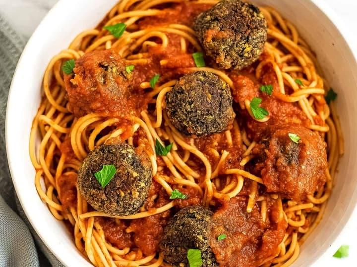 Spaghetti and quinoa lentil meatballs in a white bowl.
