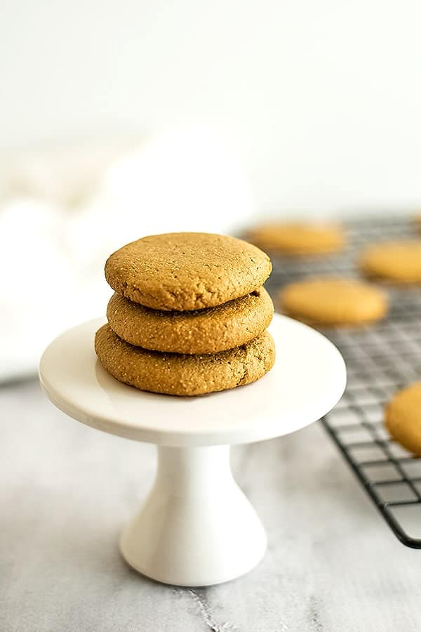 3 sunbutter cookies stacked on a white pedestal.