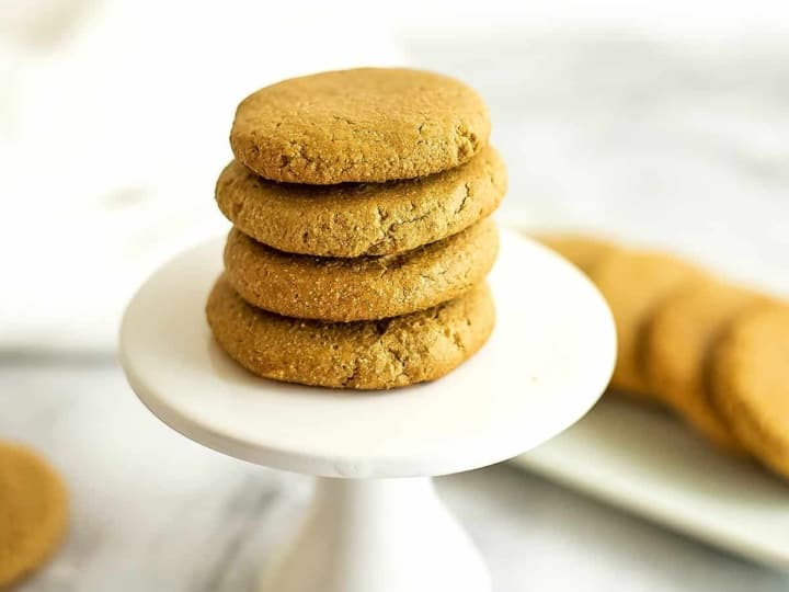 4 sunbutter cookies stacked on a white pedestal.