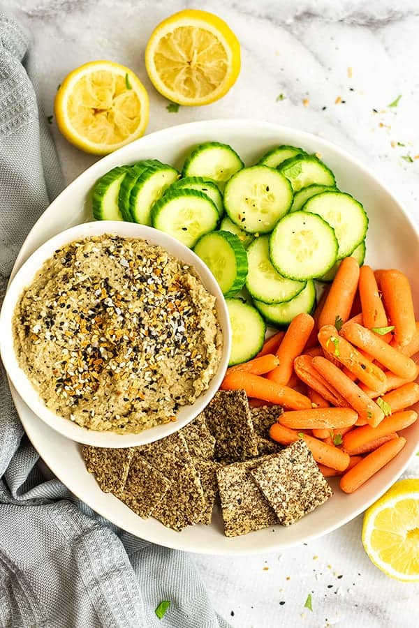 Everything bagel hummus on a tray with other veggies.