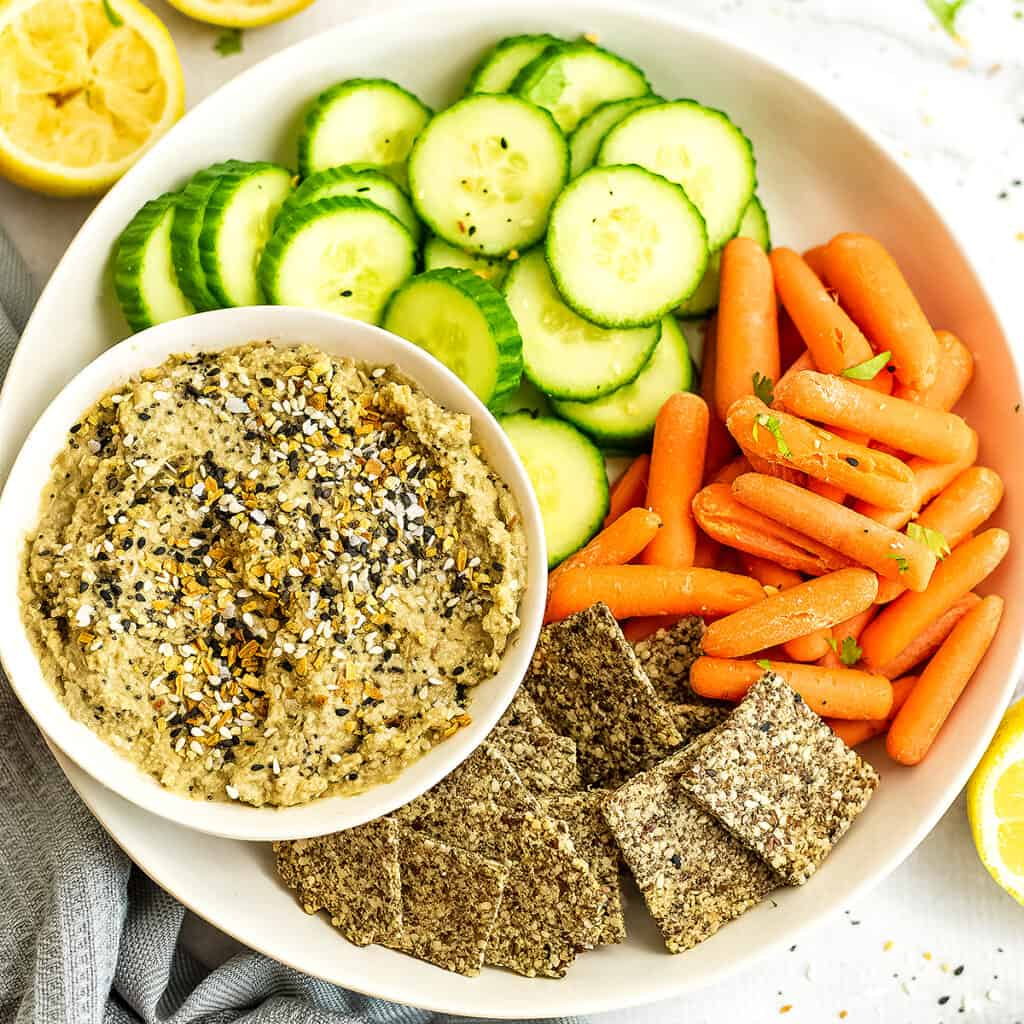 Tray with everything bagel hummus and cucumbers and carrots.