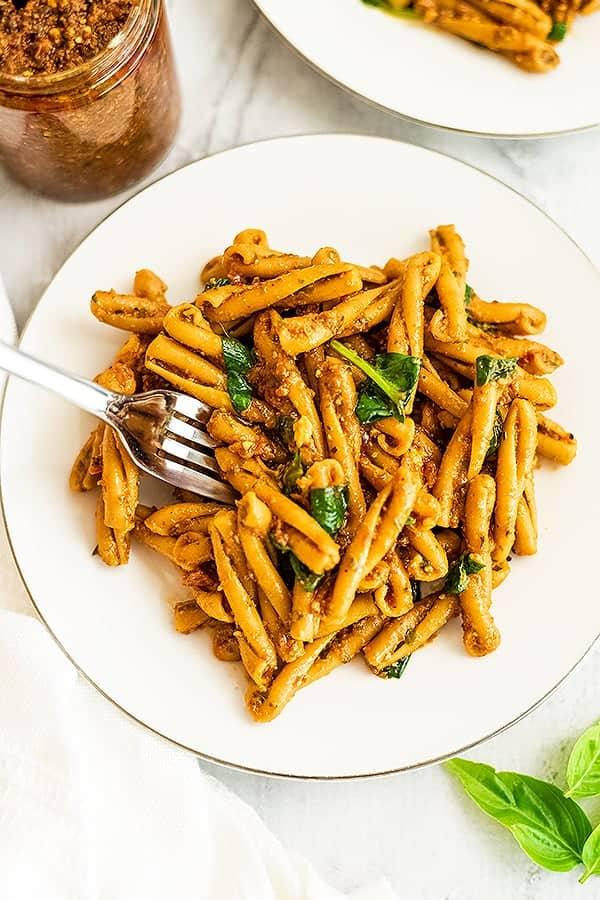 Fork picking up a bite of red pesto pasta.