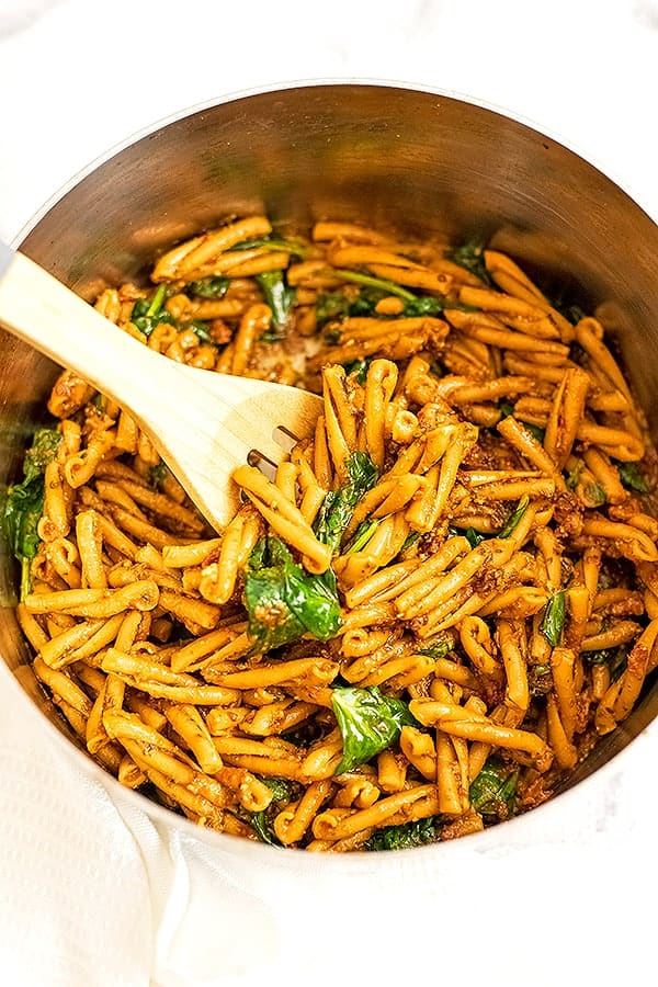 Wooden spoon in pot with red pesto pasta.