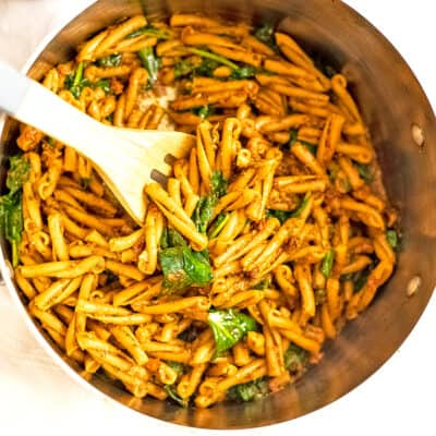 Pot filled with sundried tomato pesto pasta with wooden spoon.