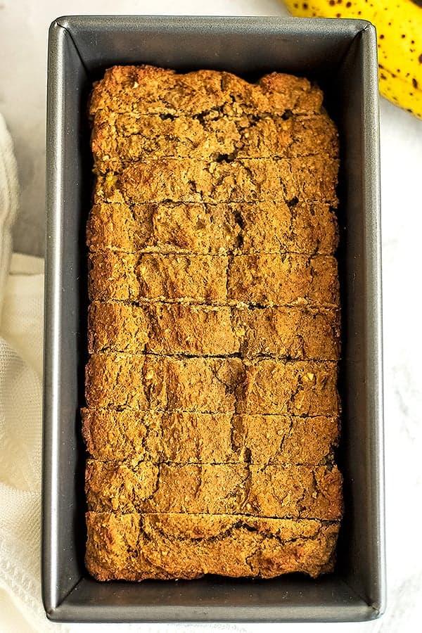 Vegan protein banana bread in a loaf tin, sliced.