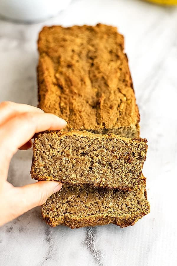 Protein banana bread cut into slices on a white serving platter.