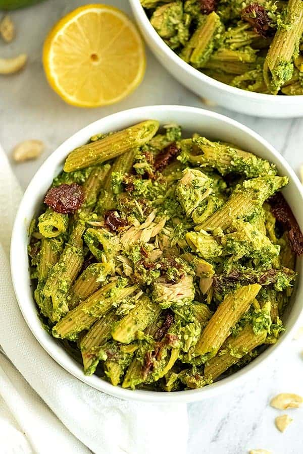Tuna pesto pasta in a white bowl with lemons in background.