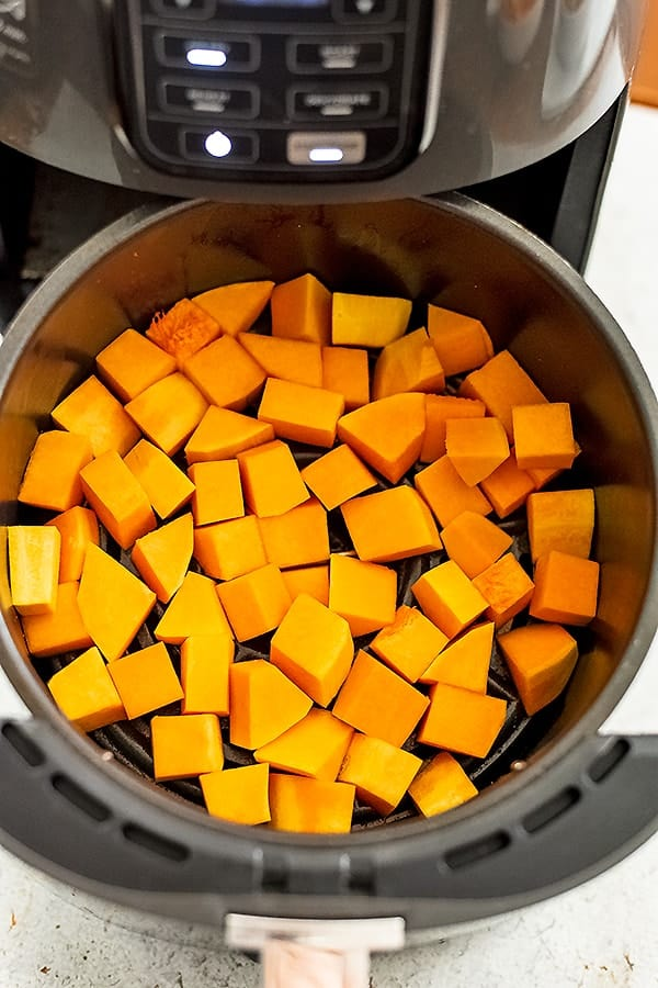 Air fryer basket filled with butternut squash cubes before cooking.