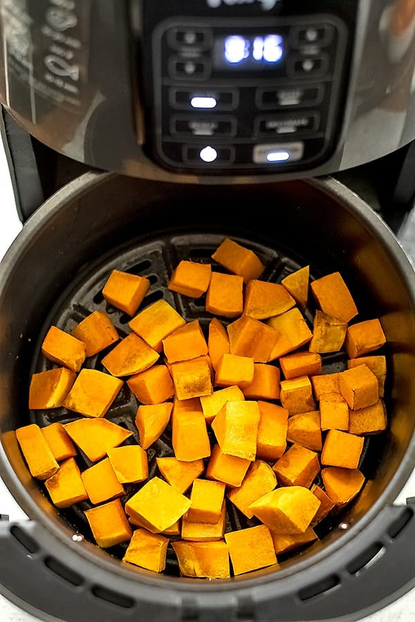 Air fryer basket filled with butternut squash cubes during cooking.