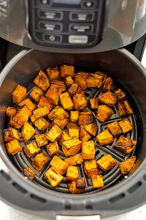 Air fryer basket filled with butternut squash cubes after cooking.