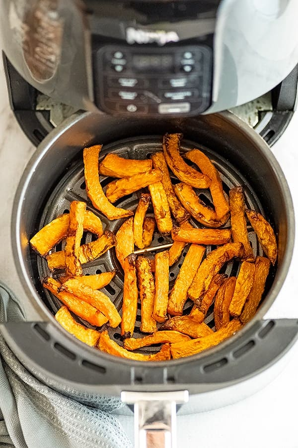 Air fryer basket filled with butternut squash fries.